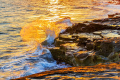 Waves crashing against the rocks. In sunset rays Royalty Free Stock Images