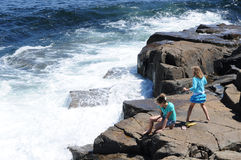 Waves crashing against rocks. Two young girls watching the waves from the Atlantic Ocean crash against the rocks at Schoodic Peninsula, Acadia National Park Stock Photo