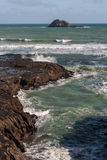 Waves crashing against volcanic rocks at Muriwai beach Stock Photography