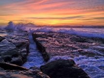 Waves crashing along rocky beach with dramatic sunset Stock Images