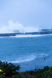 Waves crashing into barrier wall. Barrier wall at beach with crashing waves during storm Stock Images