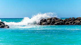 Waves crashing on the barriers made of large rocks at the resort community of Ko Olina. On the West Coast of the Hawaiian island of Oahu. The barriers make the royalty free stock image