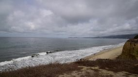 Waves crashing on the beach. With overcast skies. California coastline USA stock video footage