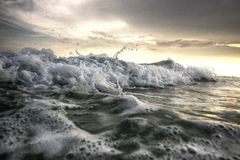 Waves crashing on the beach. Close up shot of waves crashing on the surf under a beautiful sunny beach day royalty free stock photography
