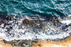 Waves crashing breaking on the rocks. Drone aerial sea surface view. Aerial view with drone on the seashore where the waves crashing on the rocks rocky. Foam and stock photography