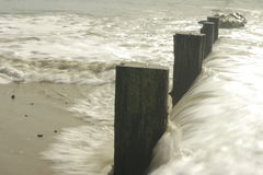 Waves crashing on breakwater. On beach, long exposure Royalty Free Stock Images