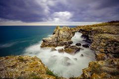 Waves, crashing on the cliffs. A clear view of the horizon, cloudy, ominous sky stock photos