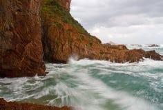 Waves crashing into cliffs Stock Photo