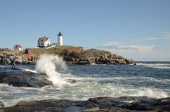 Waves crashing in front of Nubble lighthouse, Cape Nedick Maine. Waves crashing in front of Nubble lighthouse, Cape Neddick, Maine. Blue sky with clouds Royalty Free Stock Images
