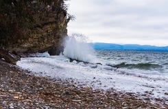 Waves crashing on frozen lakeshore Stock Photo