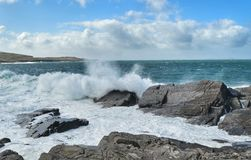Waves crashing in Ireland. Waves crash against the rocks near Valentia Island Lighthouse, Co. Kerry, Ireland, on a blustery sunny afternoon Royalty Free Stock Image