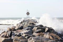 Waves crashing on jetty rocks. On a summer sunny day Royalty Free Stock Photo