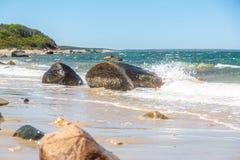 Waves crashing on large boulder in the ocean on Martha`s Vineyard, Massachusetts, USA stock photo