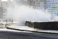 Waves crashing on the Malecon of Havana, Cuba, the people getting wet royalty free stock photos
