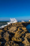 Waves crashing on man made rocky barrier.  Royalty Free Stock Photo