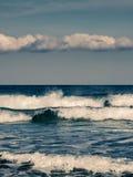 Waves crashing onto beach in Corsica Stock Photo