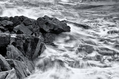Waves crashing onto a rocky ledge Royalty Free Stock Image