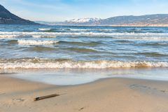 Waves crashing onto sandy beach with snow-capped mountains in distance and blue sky royalty free stock photo