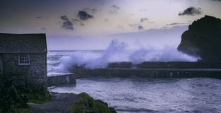 Stormy ocean waves break over harbour wall
