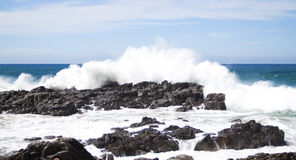 Waves crashing over rocks Stock Images