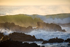 Waves crashing over rocks from the ocean's incoming morning tide.  Stock Images