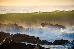Waves crashing over rocks from the ocean's incoming morning tide.  Royalty Free Stock Photography