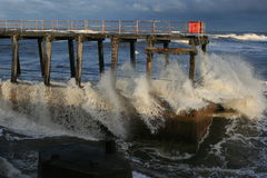 Waves crashing into pier Stock Image