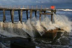 Waves crashing into pier Stock Image