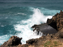 Waves crashing on the rocks. Looking down on waves crashing on a a rocky outcrop from a cliff face Stock Image
