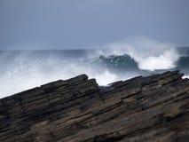 Waves crashing on rocks Stock Images