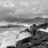 Waves crashing on rocks on Baker Beach with Marin Headlands and rain clouds in the background in black and white stock images