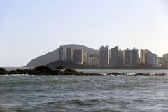 Waves crashing on the rocks in Guaruja, Sao Paulo, Brazil. With city in background stock images