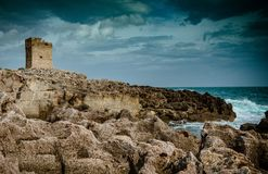 Waves crashing on rocks and old medieval tower on top stock images