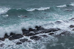 Waves crashing rocks at an overcast day Royalty Free Stock Photos