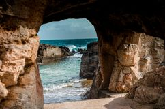Natural cave from which you an see the ocean royalty free stock photo