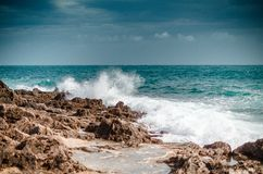 Waves crashing on rocks and storm coming. Nice spray and white waves royalty free stock photo