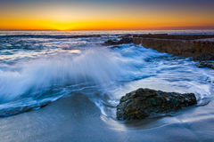 Waves crashing on rocks at sunset  Stock Image