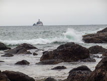 Waves Crashing on Rocks with Tillamook Lighthouse Royalty Free Stock Photos