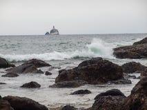 Waves Crashing on Rocks with Tillamook Lighthouse Royalty Free Stock Photos