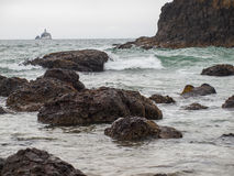 Waves Crashing on Rocks with Tillamook Lighthouse Stock Image