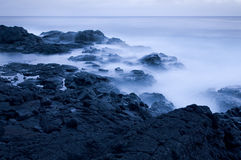 Waves crashing on rocky coast at dusk Royalty Free Stock Images