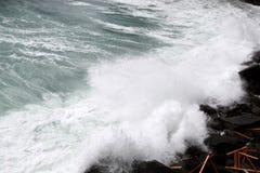 waves crashing on the rocky coast of northern Italy o Stock Photos