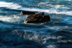 Waves crashing on rocky coastline, abstract. Dramatic background of ocean at dusk on Asilomar State Marine Reserve, Pacific Grove near Monterey and Big Sur Stock Photography