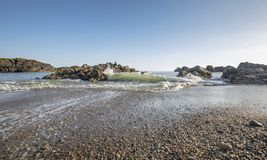 Waves Crashing on Rocky Shore at Low Tide stock photo