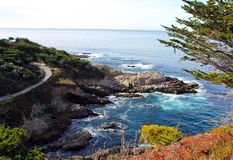 Waves crashing the rocky shoreline Carmel, California. Viewpoint on the outskirts of Carmel, California with waves hitting the shoreline.  Pacific ocean waters Royalty Free Stock Photo