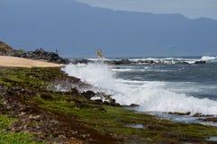 Maui Coastline. Waves crashing on Rugged Maui coastline with mountains in the background royalty free stock photo