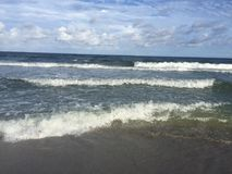 Waves crashing on the sand. On the beach stock photography