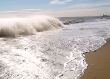 Waves crashing on sandy beach. Beautiful white and powerful waves crashing on a sandy beach on the South East Coast of England. Sunny day with waves and water Stock Image