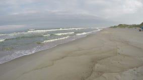 Waves crashing on sandy seashore, time lapse 4K stock video