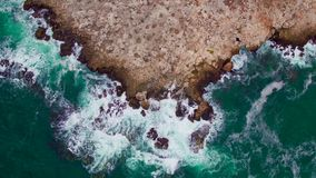 Waves crashing into the sea cliffs, aerial video stock footage